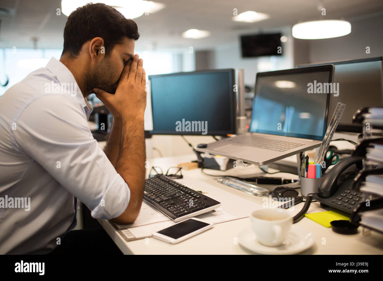 Business executive nerveux sitting at desk in office Photo Stock