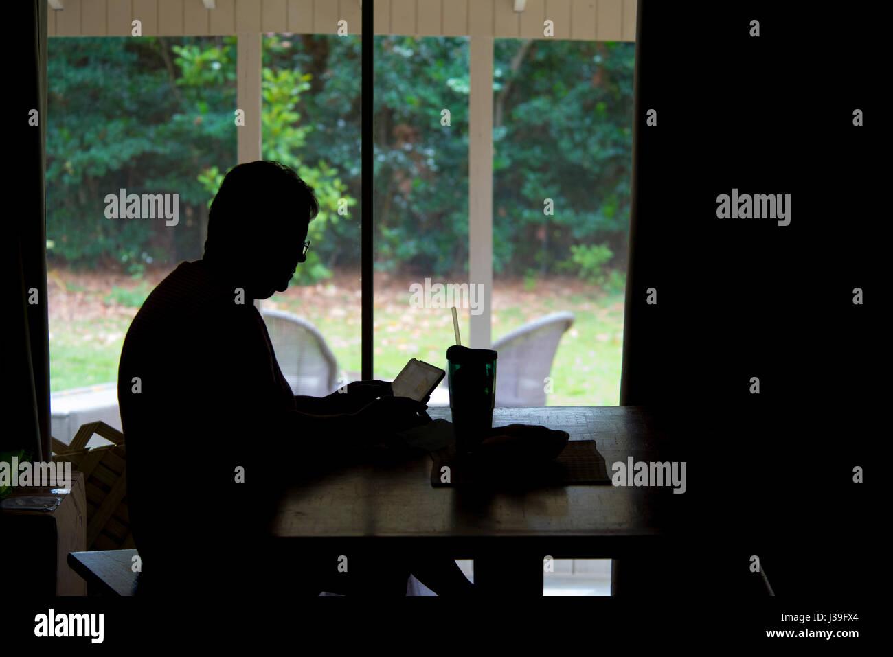 Silhouette de dame à table avec l'iPad ou ordinateur portable travailler Photo Stock