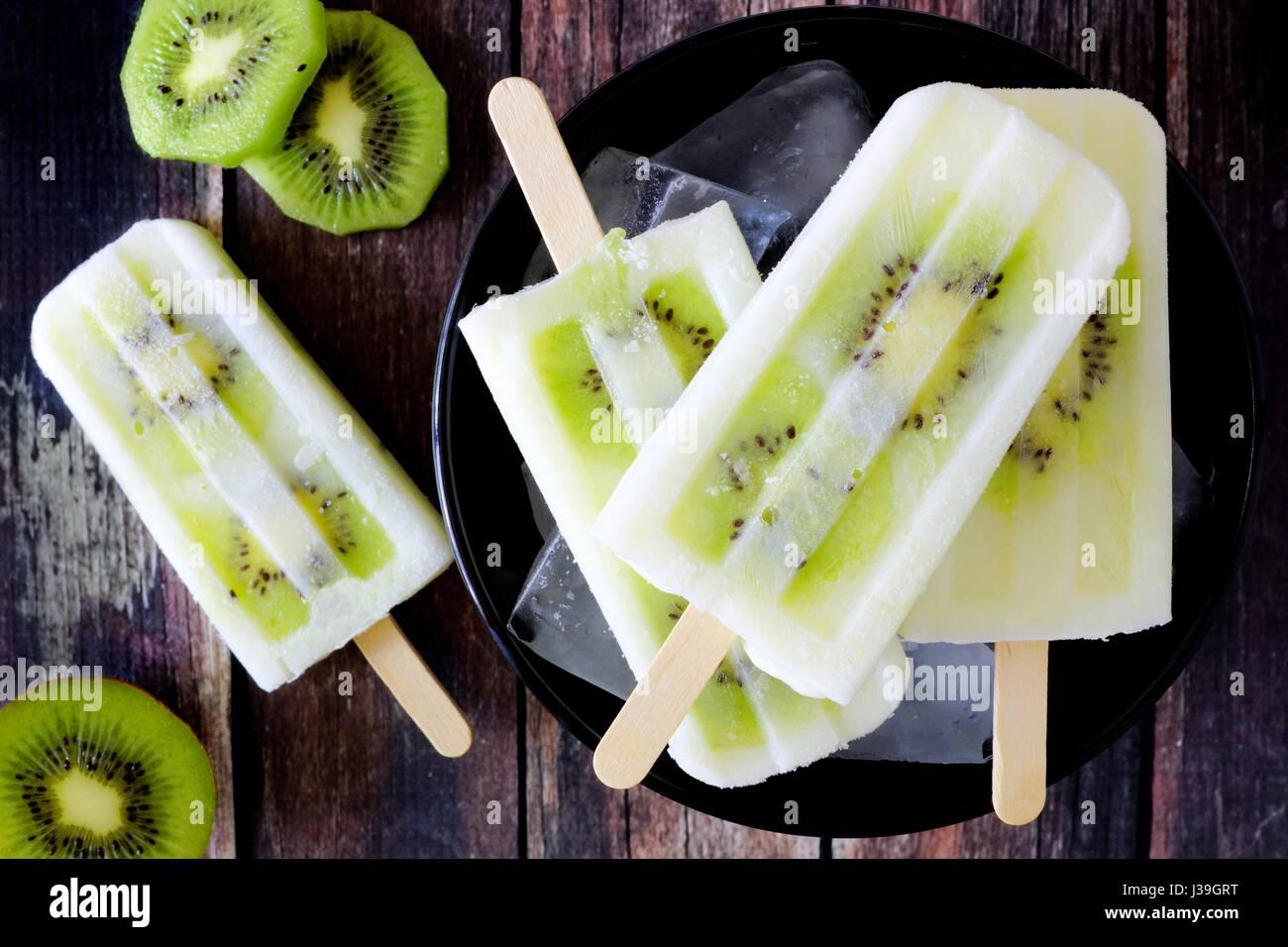 Bol de yogourt à la vanille kiwi les sucettes glacées sur un fond de bois rustique foncé Photo Stock