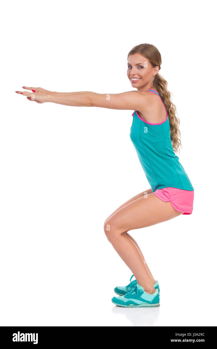 Jeune femme en rose, short et débardeur vert sneakers debout avec les bras tendus et ne un squat, vue de côté. Photo Stock