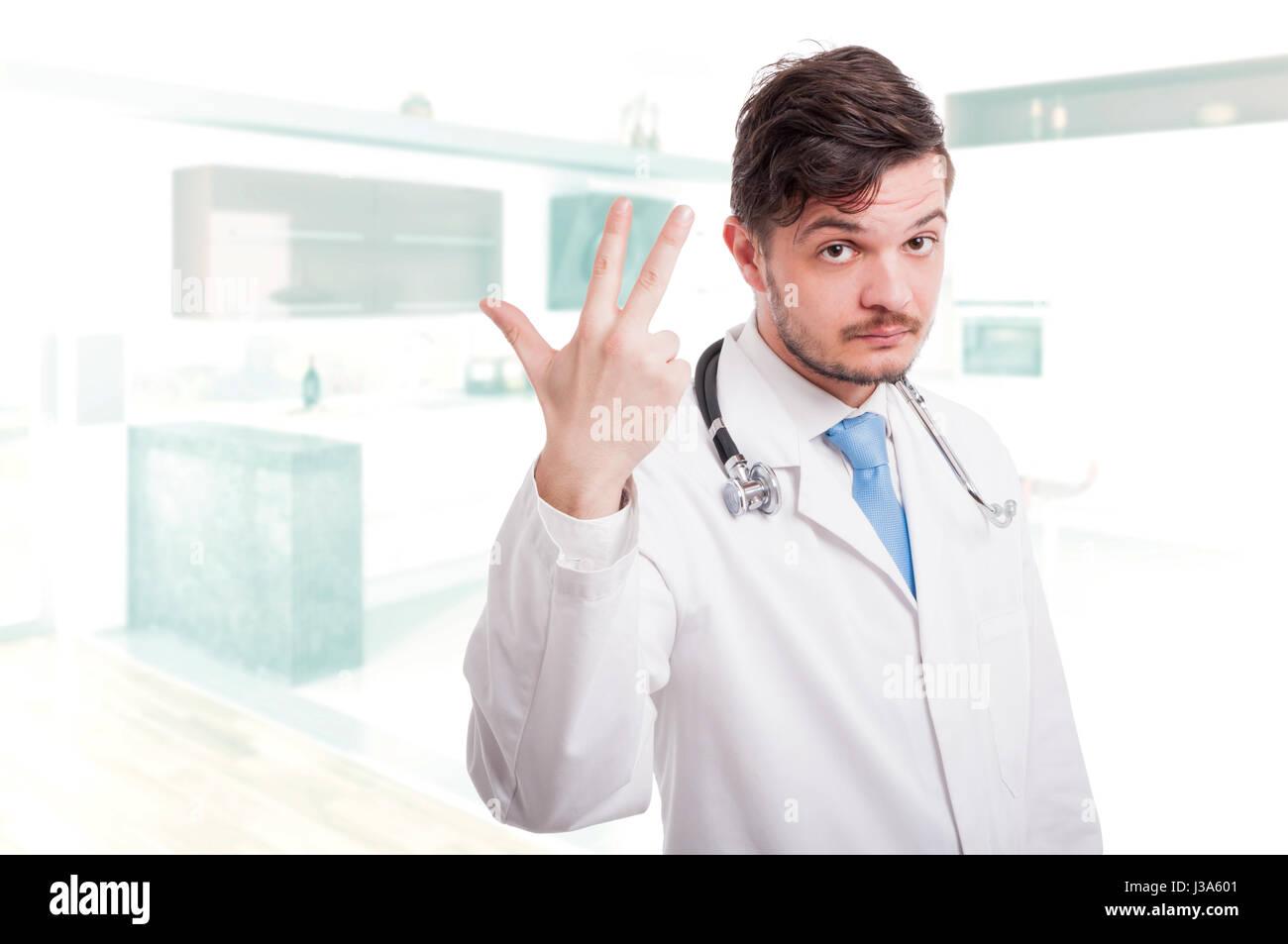 Jeune médecin montrant trois doigts vers le haut ou en comptant trois avec zone publicitaire Photo Stock