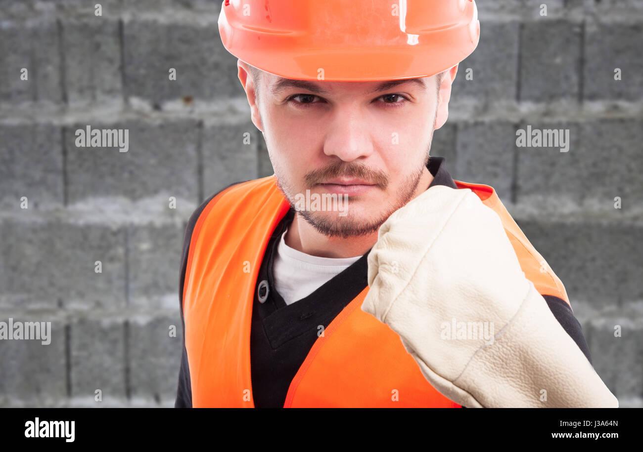 Portrait du constructeur violent montrant son poing en vue rapprochée comme concept de travail Banque D'Images
