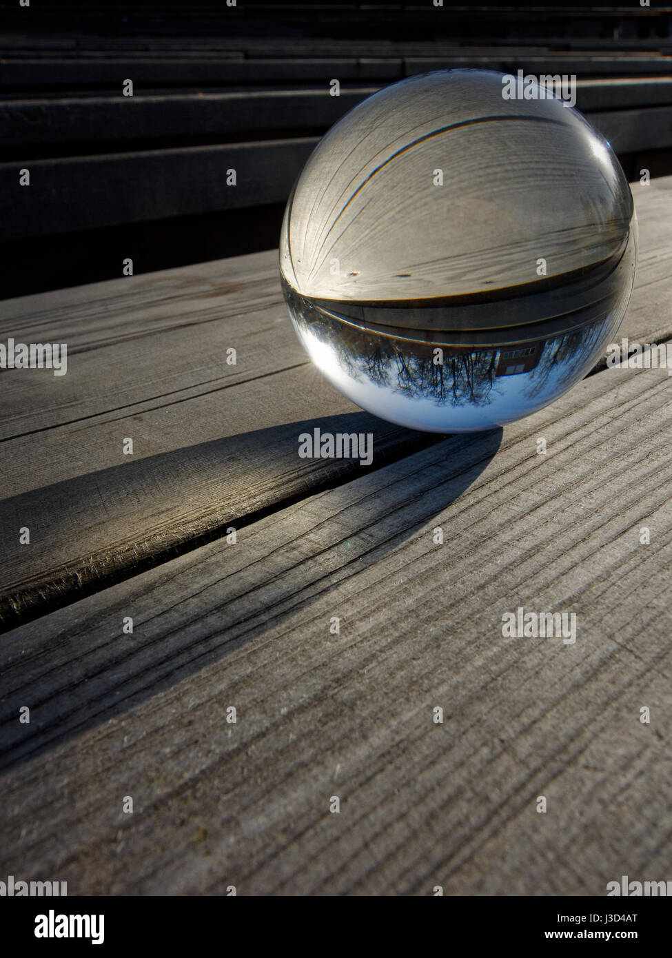 Milieux et de textures: bille de verre sur une table en bois, partie d'un paysage à l'intérieur Photo Stock