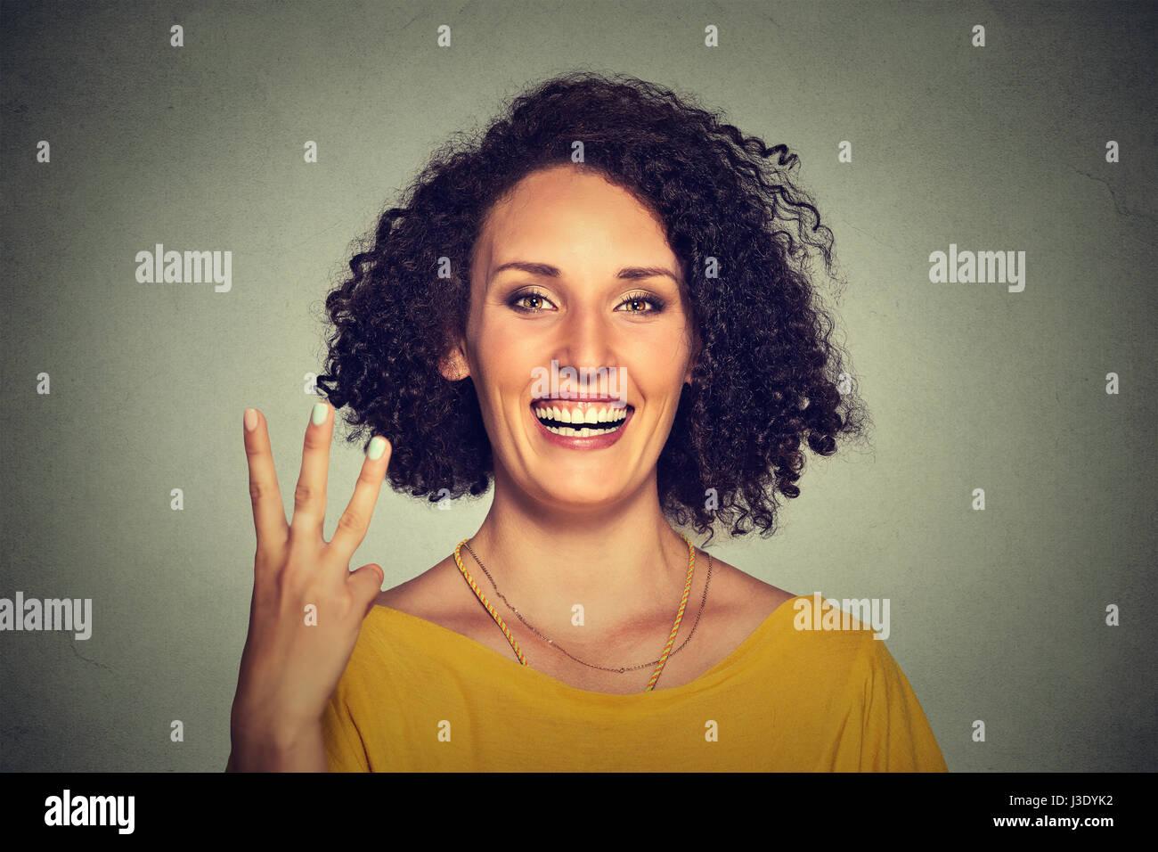Closeup portrait of young Pretty woman giving a trois doigts geste signe avec la main isolé sur fond de mur Photo Stock