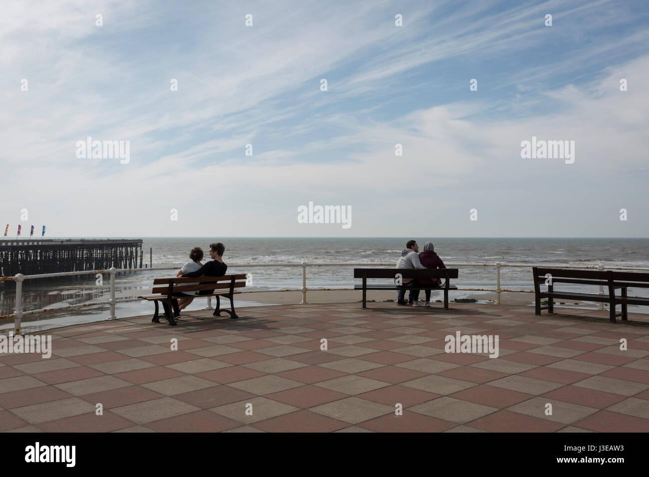 Deux couples romantiques câlins assis sur des bancs avec vue sur la mer et la jetée de Hastings, le 29 Photo Stock