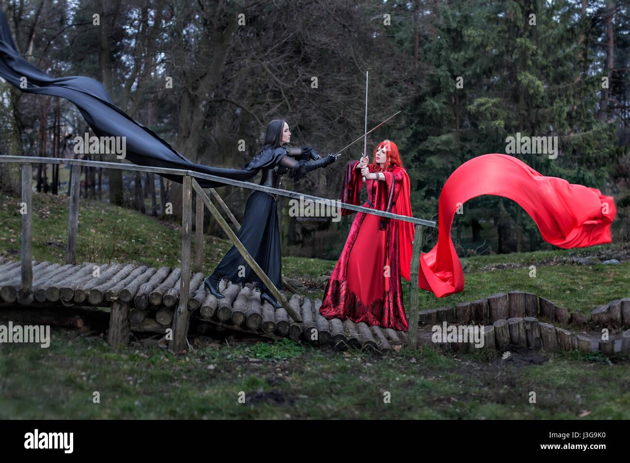 Jeune fille dans une robe vintage rouge épées bat Girl à robe noire ancienne. Photo Stock