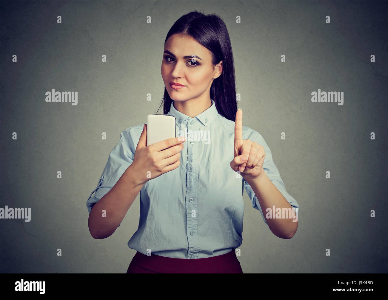 Jeune femme stricte avec le smartphone montrant pas, ne le faites pas, l'attention avec le doigt geste de la Photo Stock