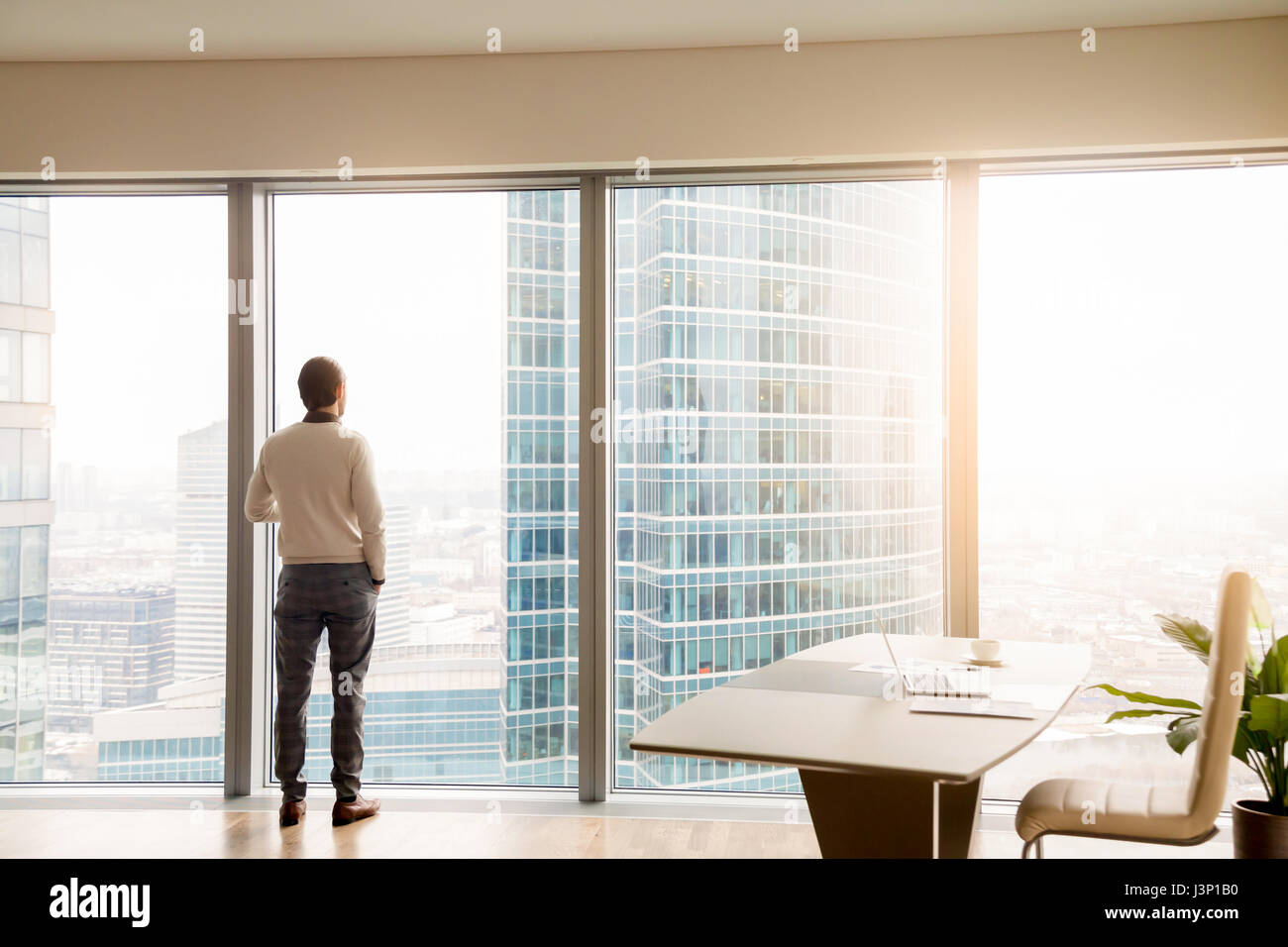 Jeune homme d'affaires réussi standing in office looking at full- Banque D'Images