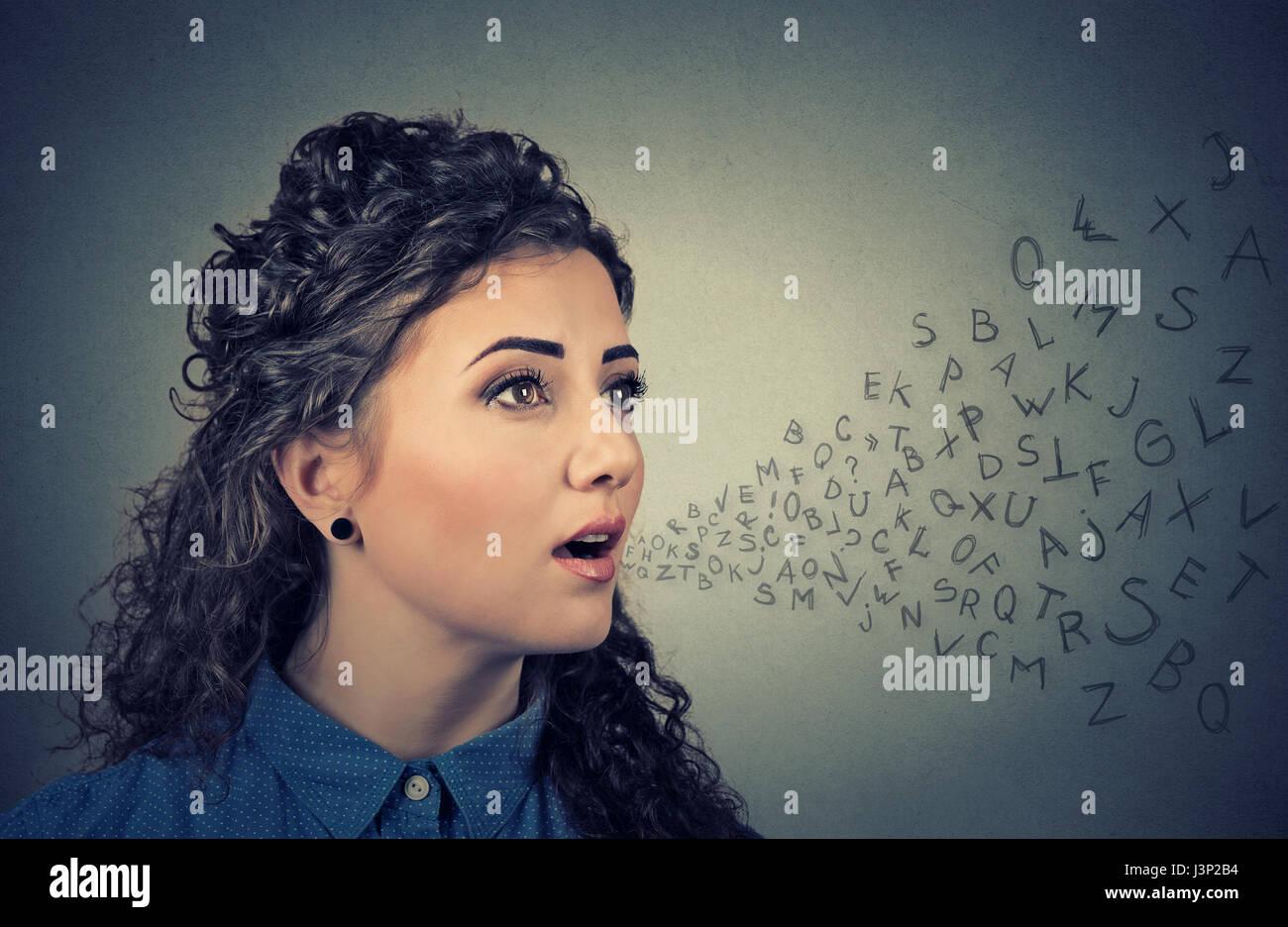 Femme parlant avec lettres de l'alphabet qui sortent de sa bouche. Communication, information, intelligence Photo Stock