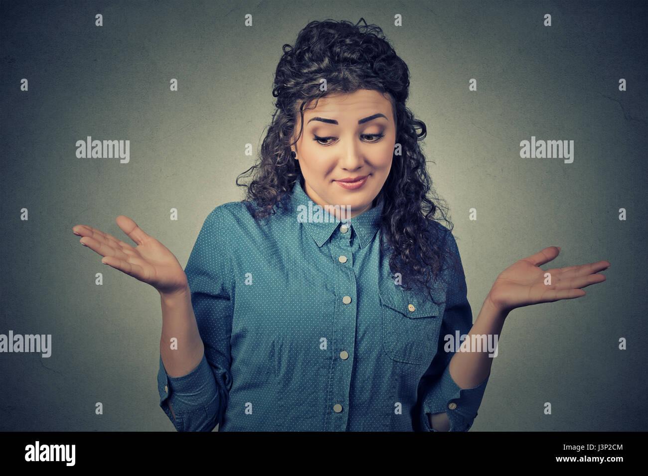 Portrait femme muette à bras à la hausse les épaules qui se soucie alors ce que je ne sais pas isolé Photo Stock
