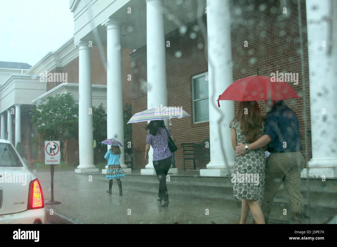 Les gens avec des parasols une marche sous la pluie Photo Stock