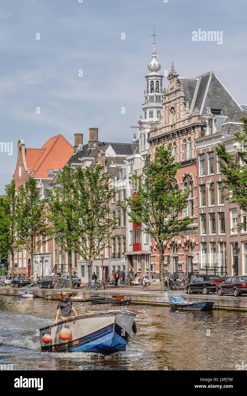 Petit bateau qui traverse un canal d'eau d'Amsterdam, Pays-Bas Banque D'Images