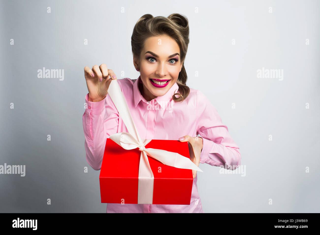 Happy funny cadeaux femme déballe Photo Stock