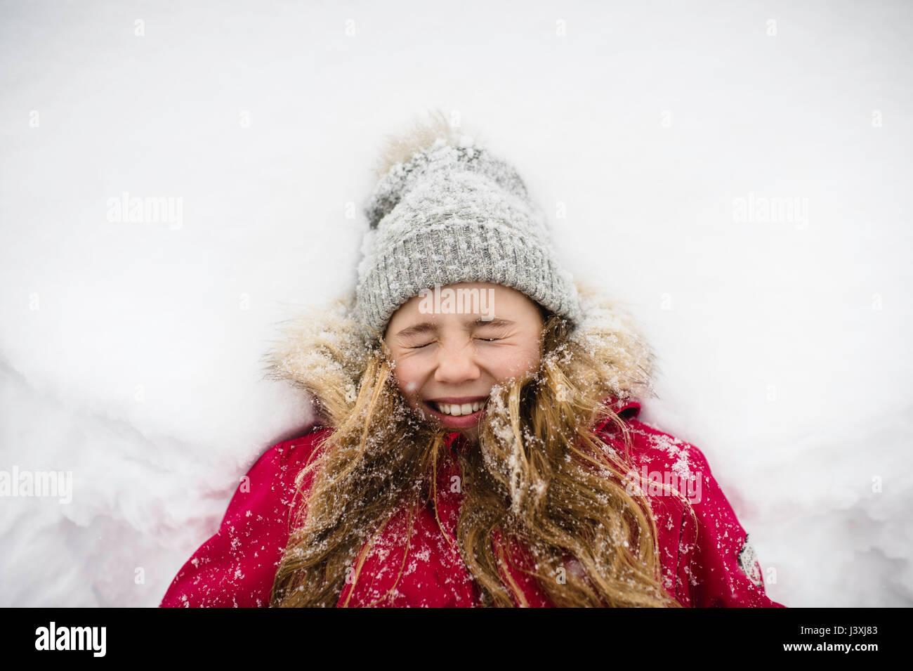 Girl allongé sur le dos dans la neige avec les yeux fermés Photo Stock