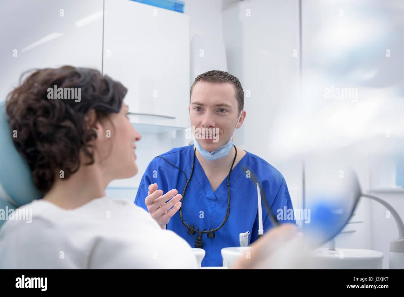 Dentiste parlant au patient en salle de traitement de chirurgie dentaire Photo Stock