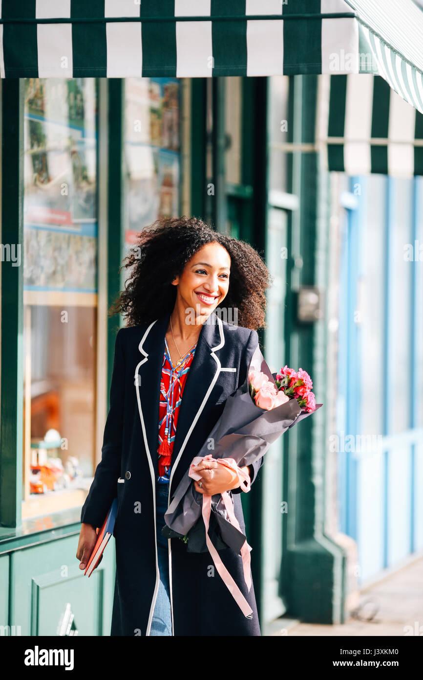 Femme élégante se promener le long de rue avec bouquet de fleurs Photo Stock