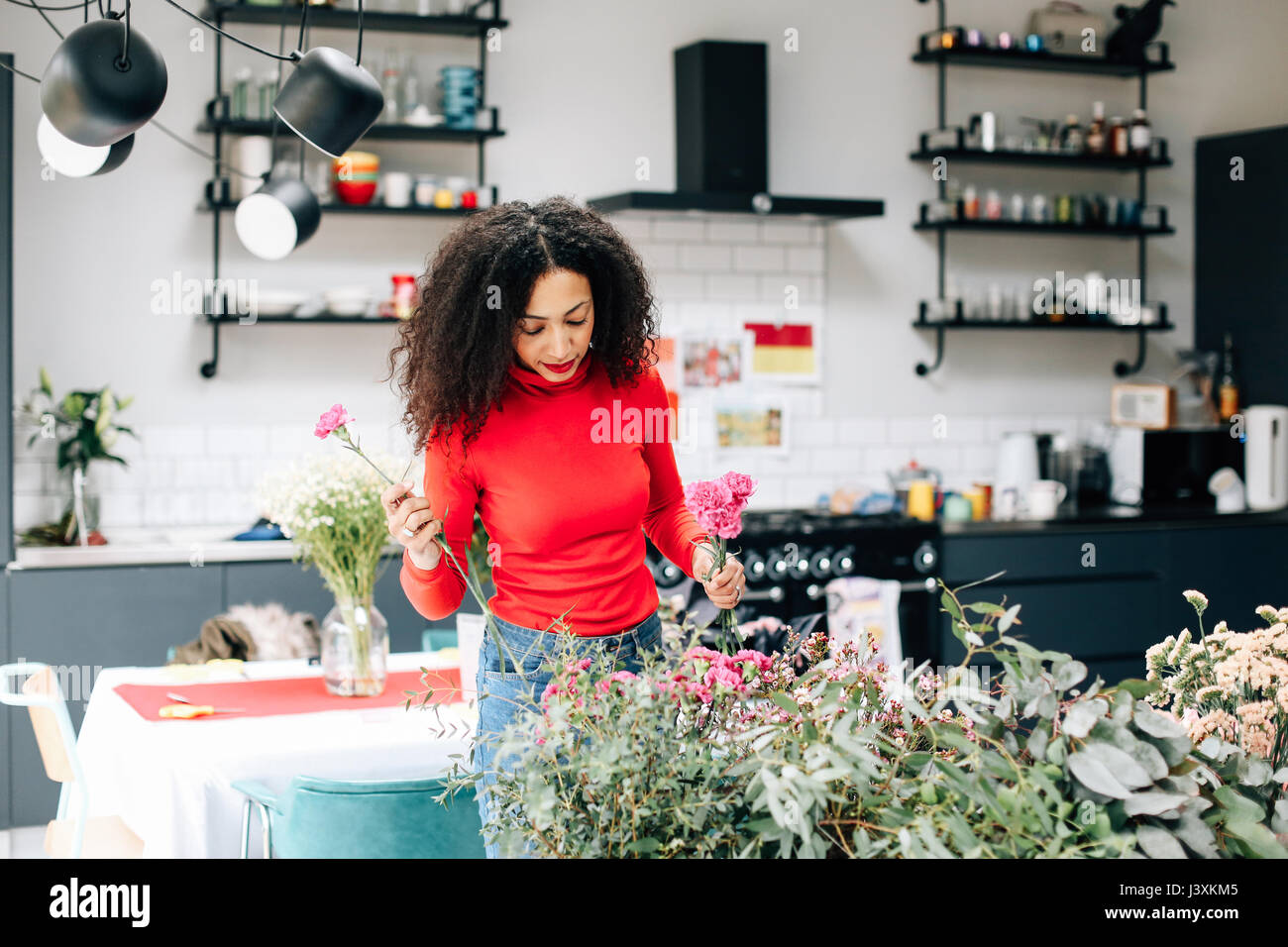 Female florist arranging flowers pour atelier floral afficher Photo Stock