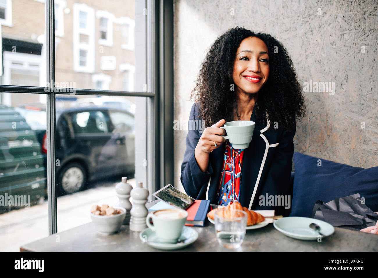 Mid adult woman holding Coffee cup in cafe Photo Stock