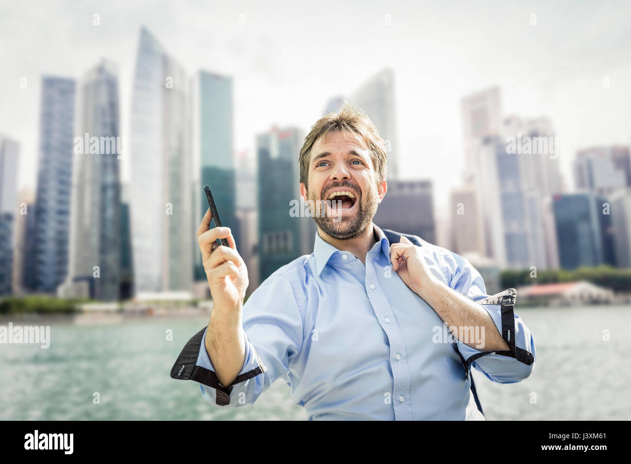 Businessman holding extatique sur smartphone city waterfront Photo Stock