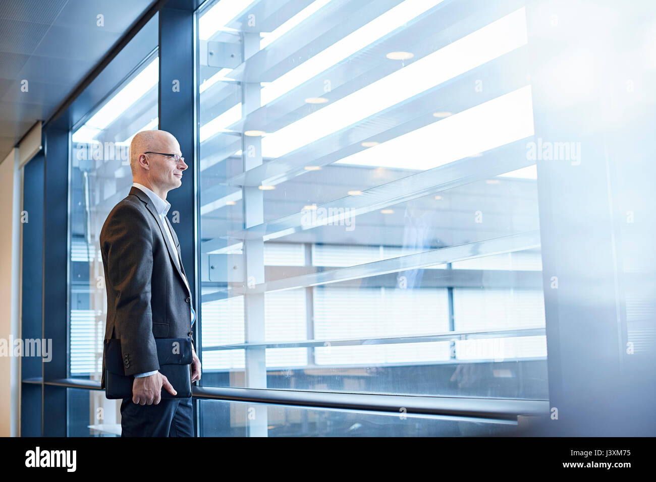Mature businessman looking through office window Photo Stock