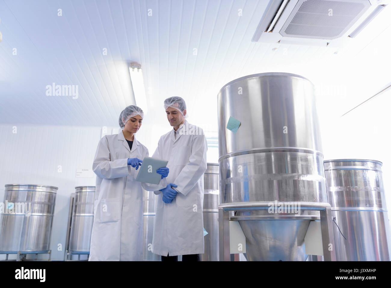 Travailleur en discussion par la TVA dans l'usine pharmaceutique Photo Stock