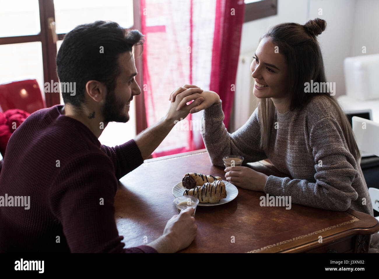 Couple sitting at table tenant les mains, boire du café Photo Stock