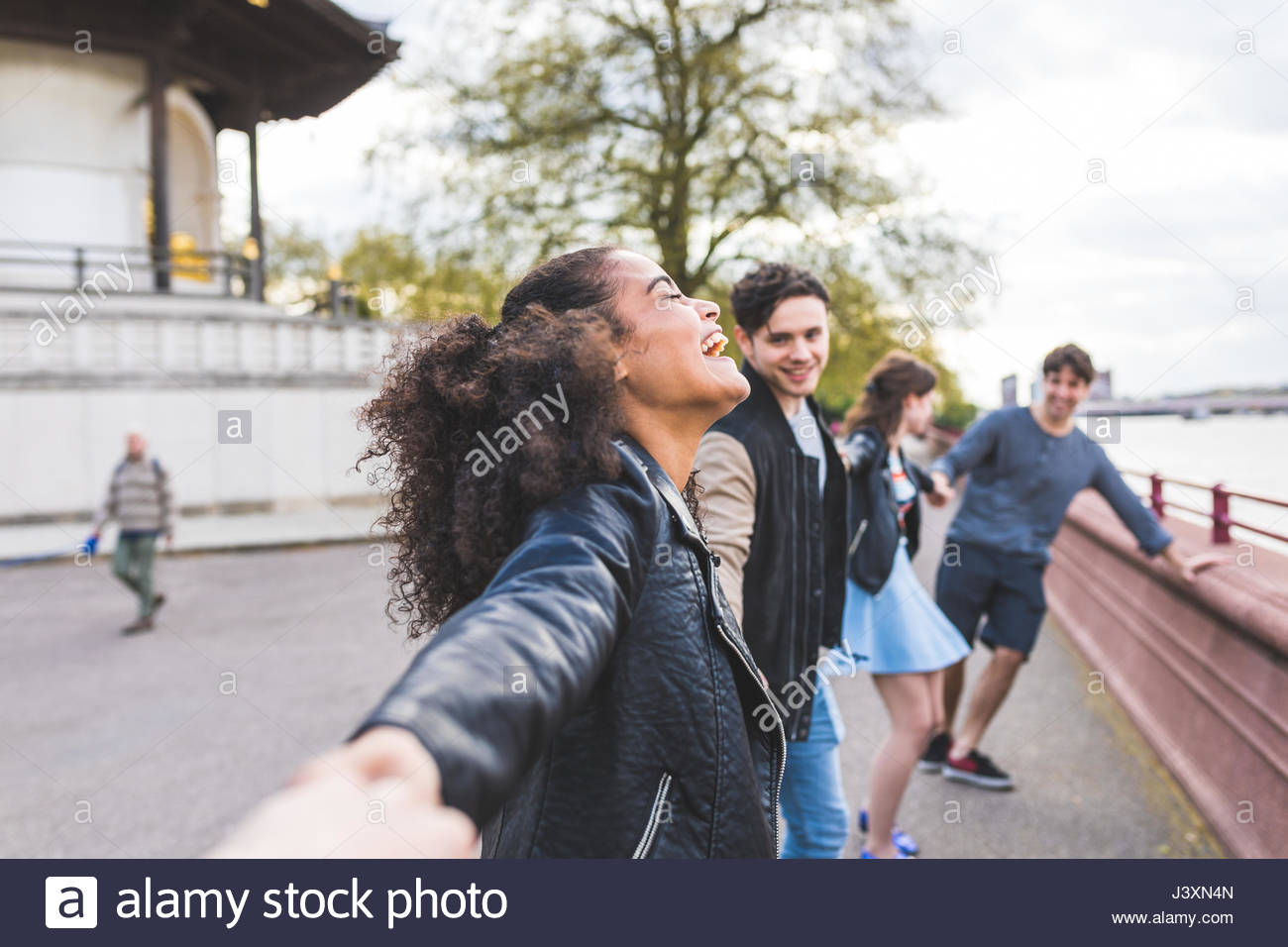 Quatre jeunes amis adultes tenant la main à Battersea Park Photo Stock