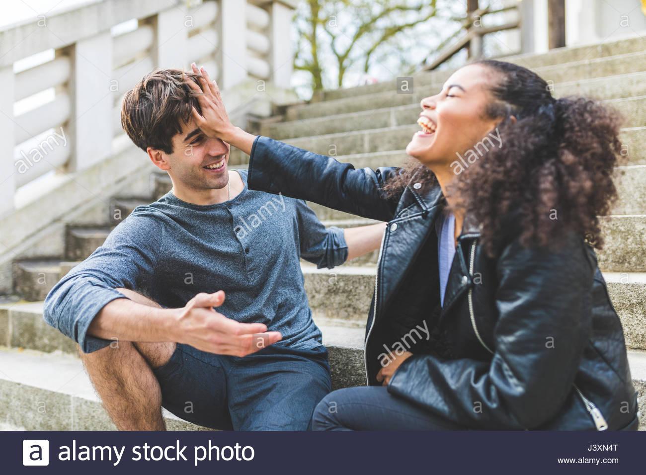 Jeune femme poussant petit ami sur escalier dans Battersea Park Photo Stock