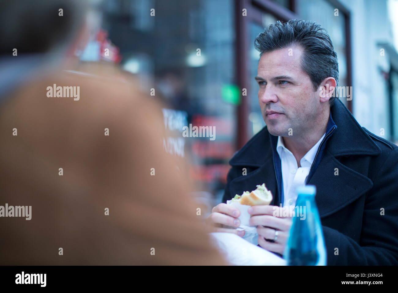 Businesspeople at cafe de la chaussée en train de déjeuner Photo Stock
