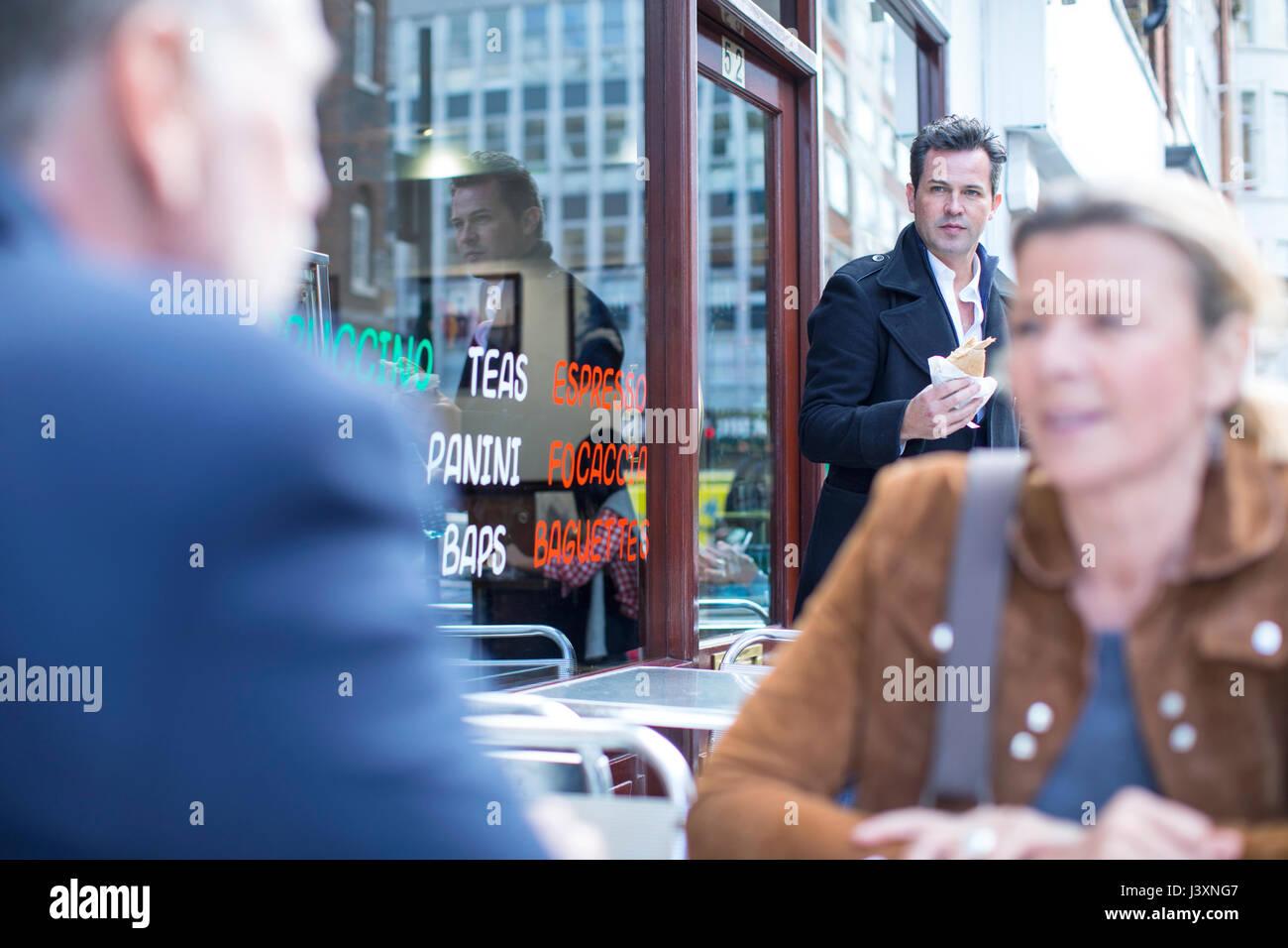 Les gens en train de déjeuner au café de la chaussée Photo Stock