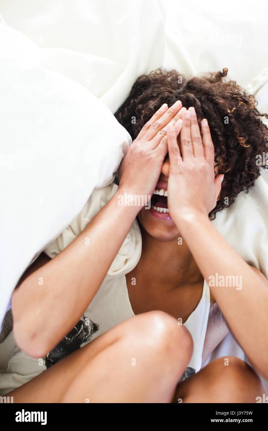 Vue de dessus de woman lying on bed couvrant ses yeux Banque D'Images