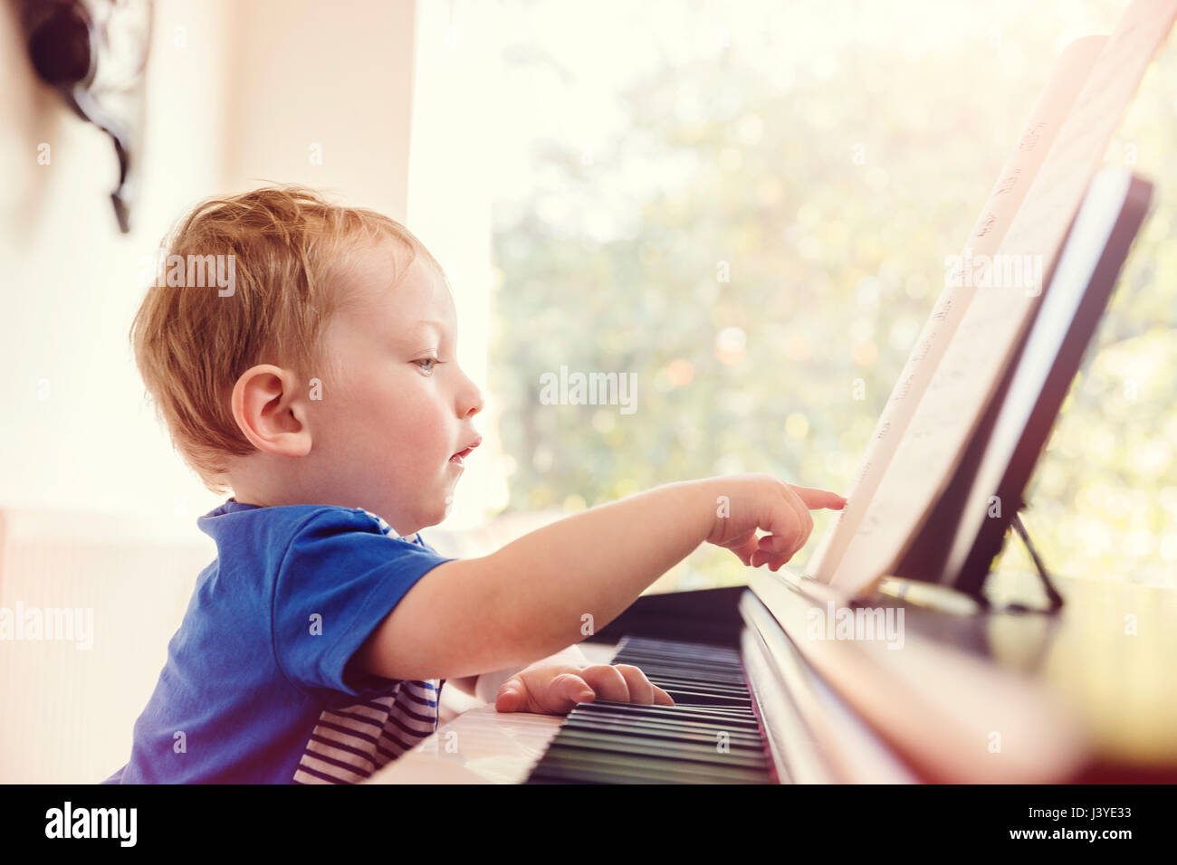 Boy toddler pointing at partition piano à Photo Stock