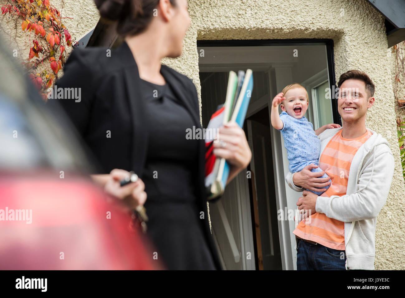 Le père et le petit garçon dites adieu à la mère à la porte d'entrée à la Photo Stock