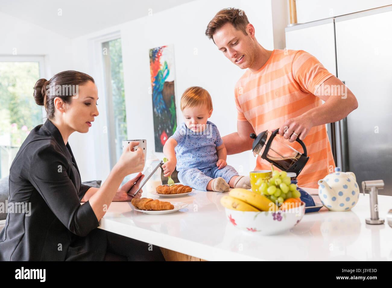 Père fait le petit déjeuner pour travailler maman et petit garçon Photo Stock