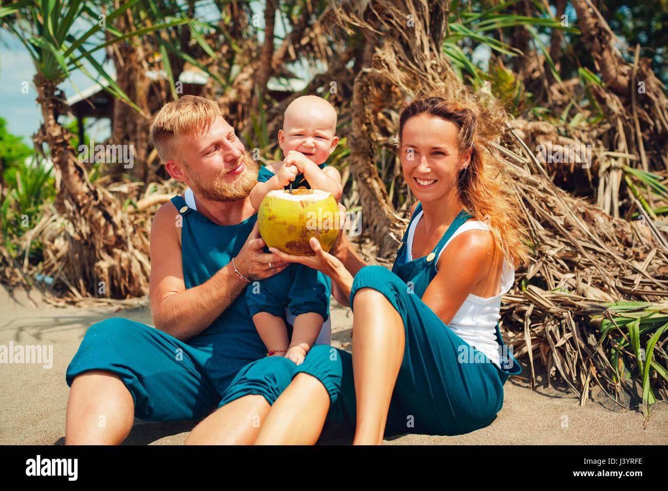 Drôle de famille heureuse pique-nique sur plage - mère, père nourrir bébé garçon. Photo Stock