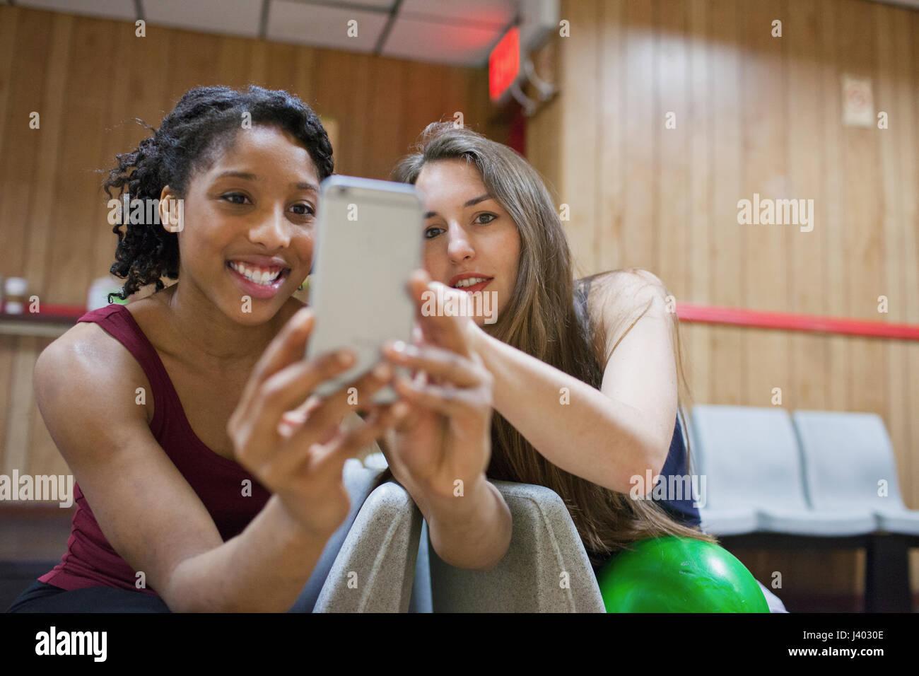 Deux jeunes femme prise d'une photo sur un téléphone cellulaire. Photo Stock