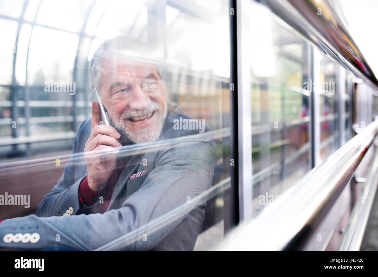 Senior man with smartphone dans le passage de verre faisant appel téléphonique. Photo Stock
