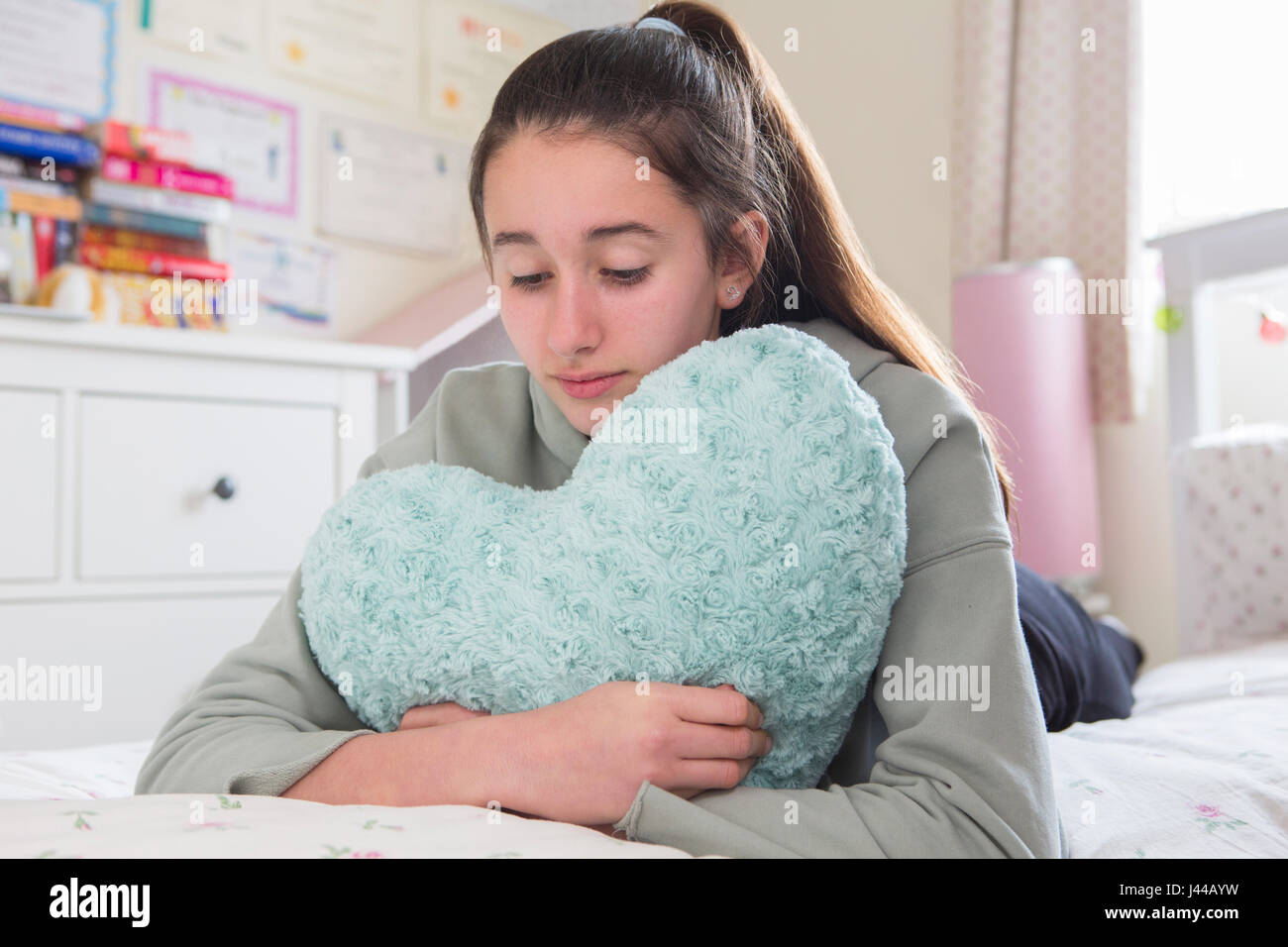 Young Girl Lying On Bed coussin en forme de coeur Hugging Photo Stock