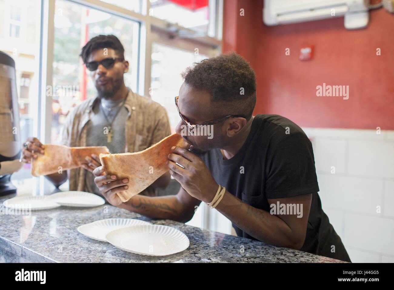 Deux jeunes hommes de manger des pizzas. Photo Stock