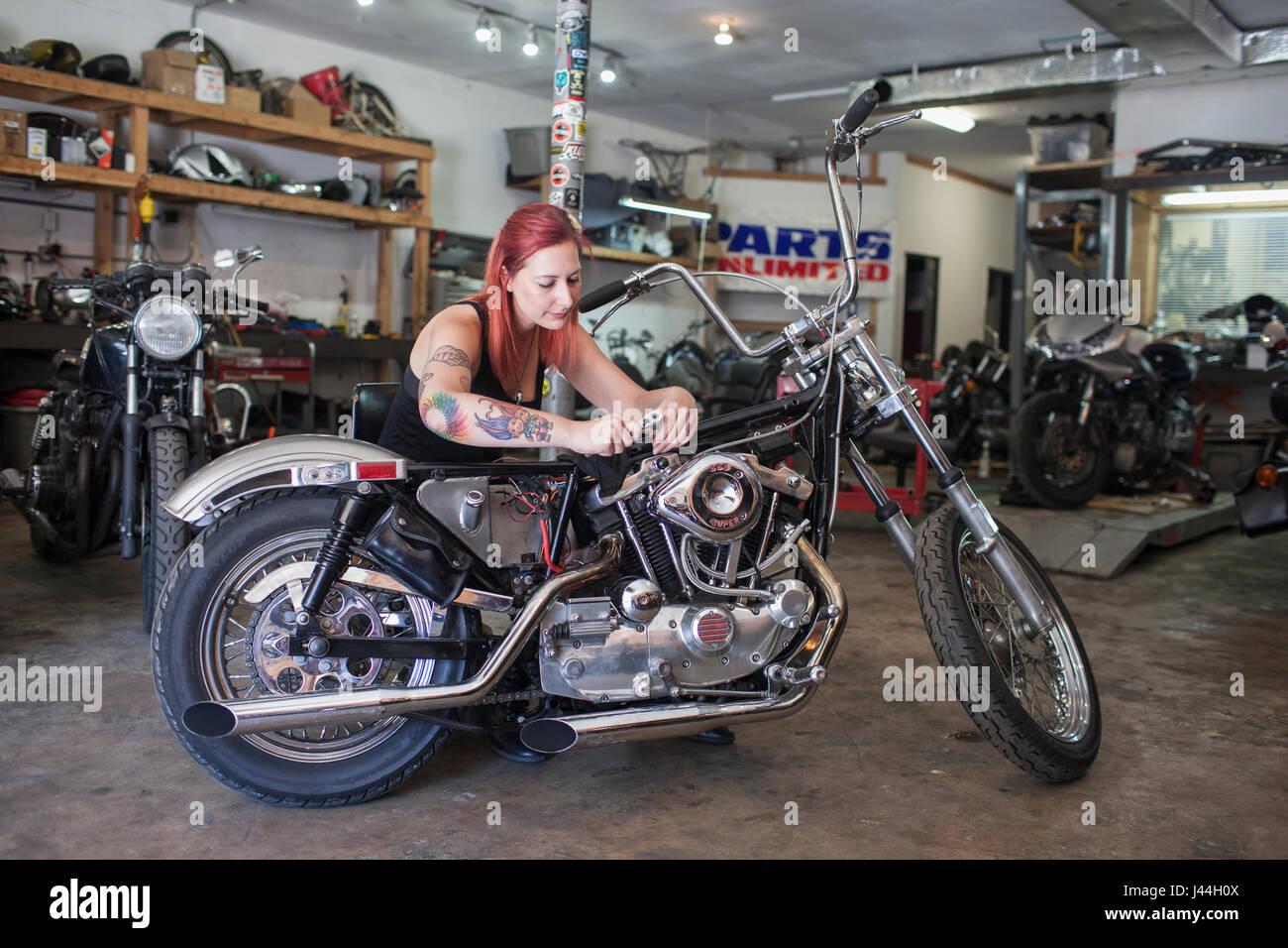 Une jeune femme repariing une moto. Photo Stock