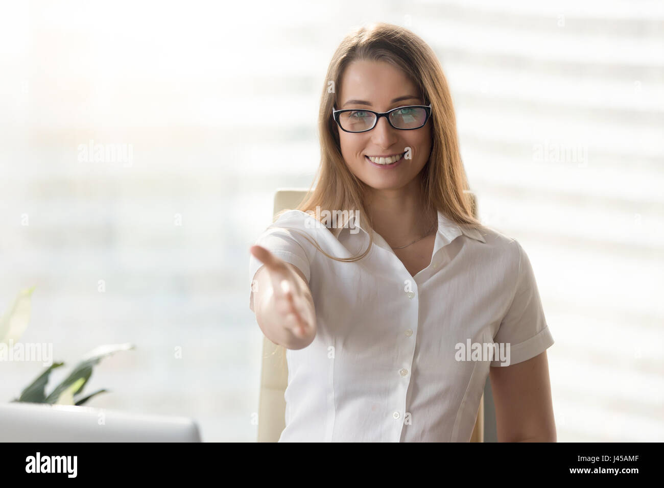 Happy businesswoman reaching hand for handshake Photo Stock