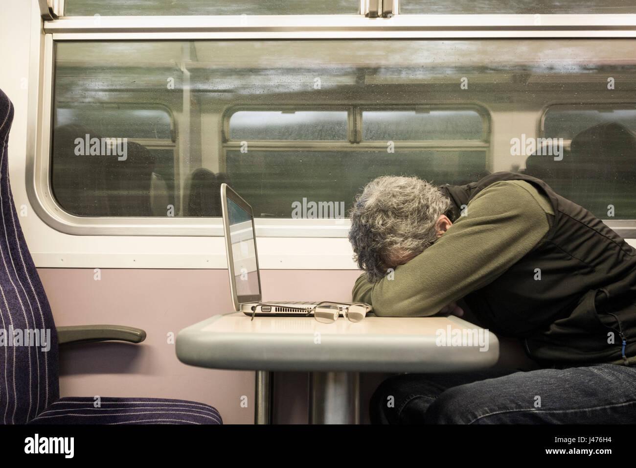 Former UK. Man with laptop dormir au siège de fenêtre sur train vide avec la pluie sur la fenêtre. Photo Stock