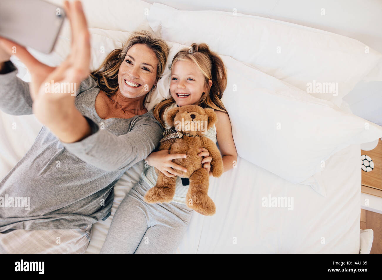 Vue d'en haut photo de Young family en tenant avec selfies smartphone dans le lit. Mother and Daughter lying Photo Stock
