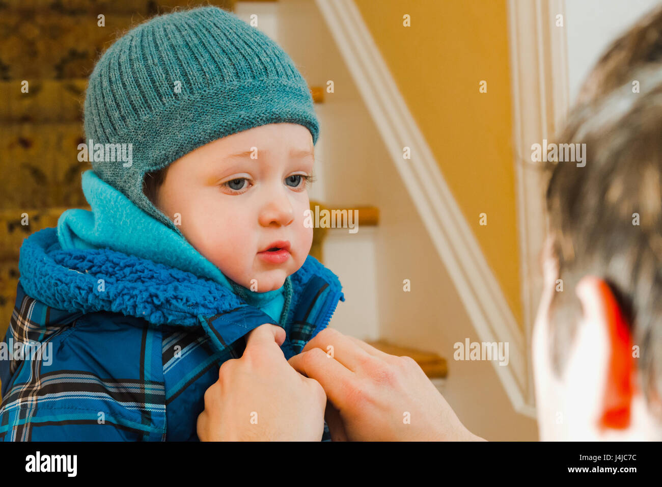 Père zipping up manteau d'hiver pour fils Photo Stock