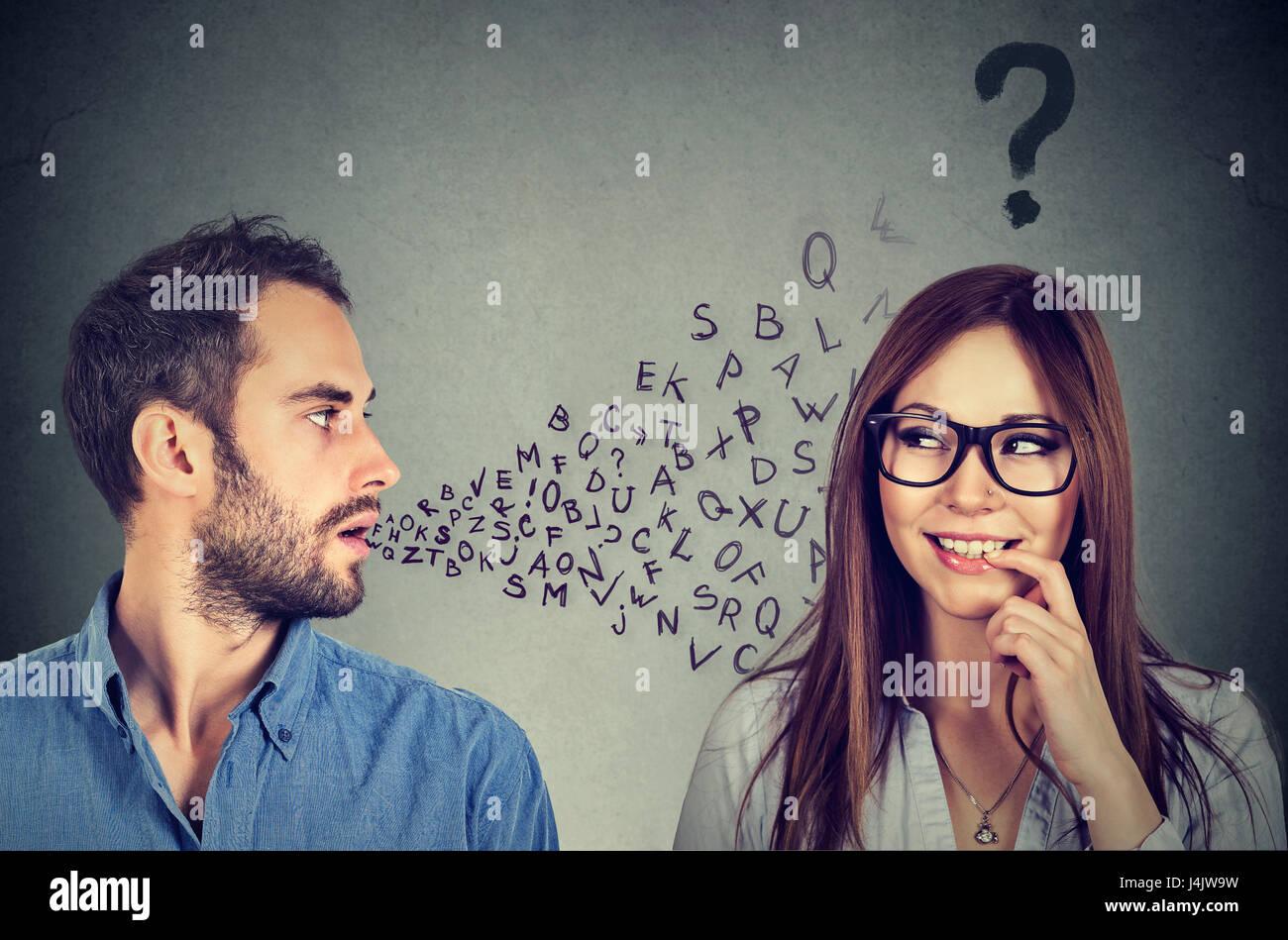 Barrière linguistique concept. Bel homme de parler à une jolie jeune femme avec un point d'interrogation Photo Stock