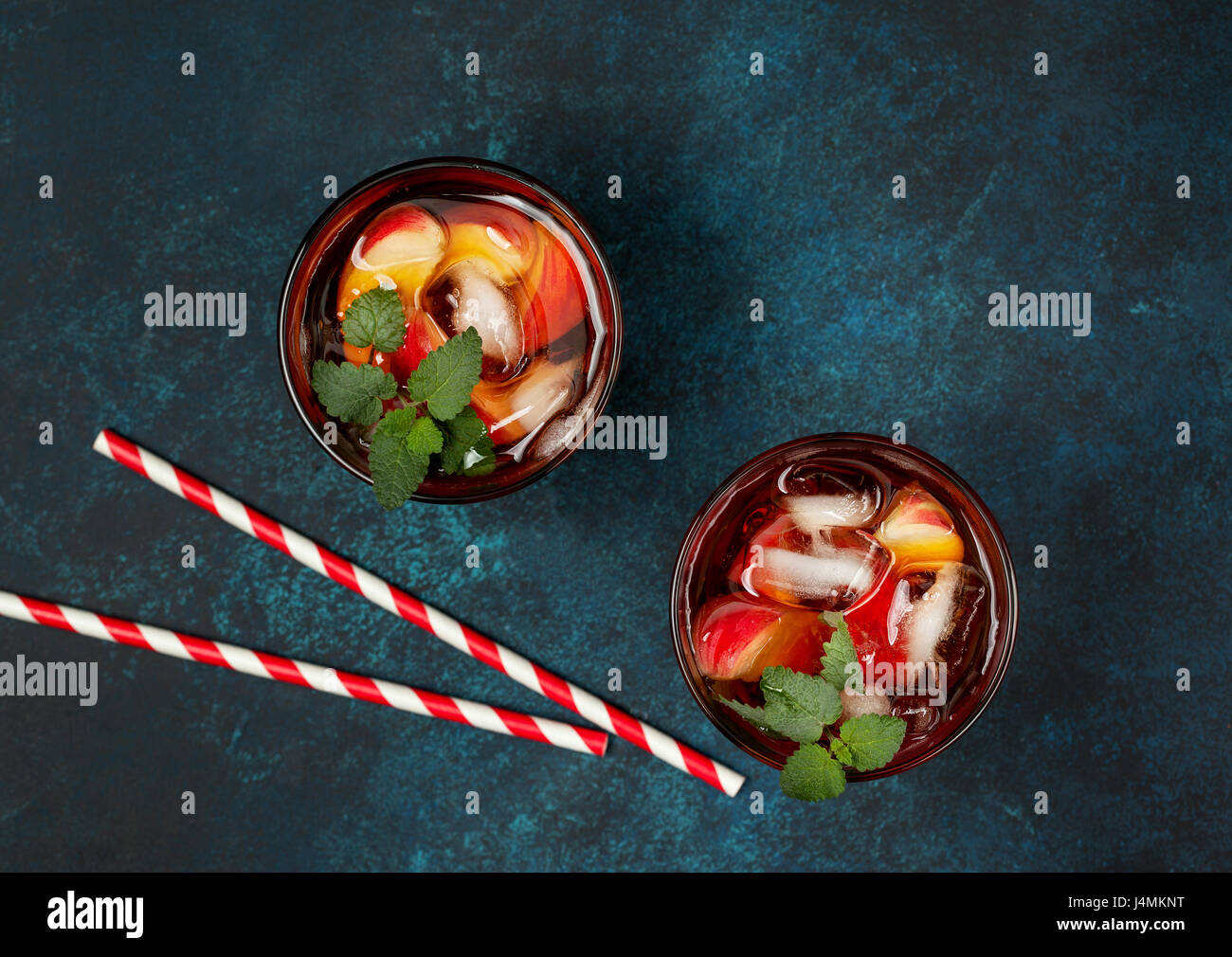 Peach thé glace en verre sur fond bleu béton. Vue de dessus Photo Stock
