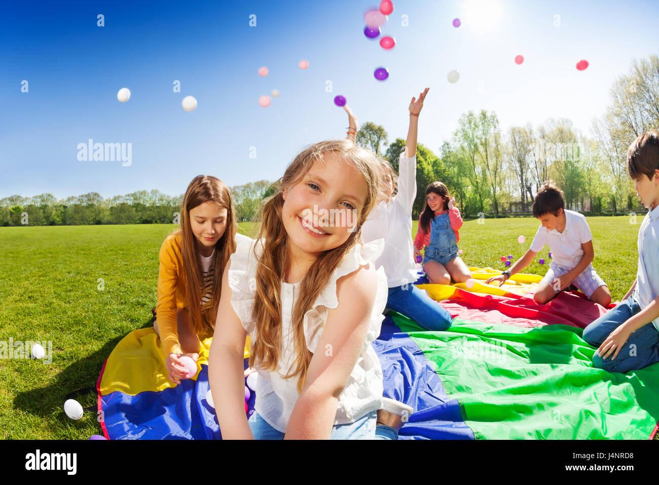 Close-up portrait of smiling blondinette, assis sur le parachute arc-en-ciel au cours du jeu avec des amis dans Banque D'Images