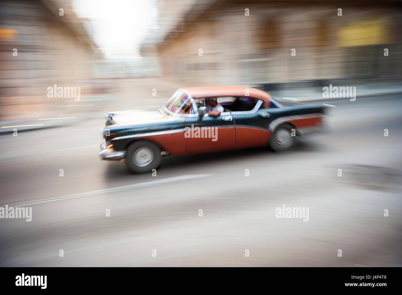 American Vintage voiture bicolore zoom taxi en face de l'effondrement de bâtiments coloniaux le front de Photo Stock