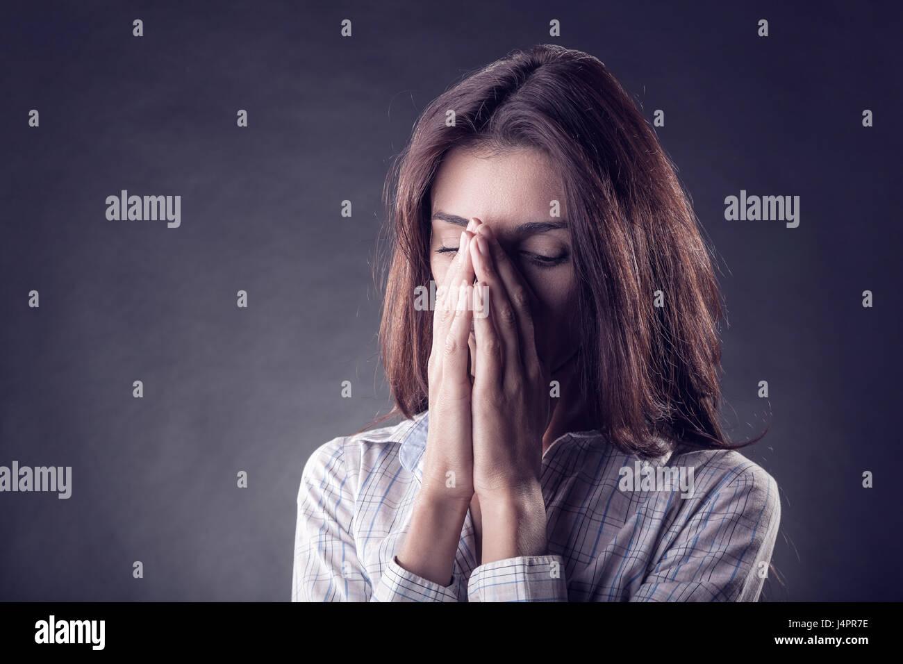 Jeune femme visage pleurant dans ses mains sur un fond noir Photo Stock