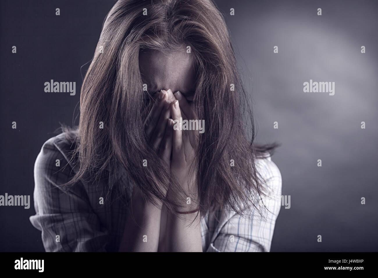 Jeune femme visage pleurant dans ses mains sur un fond sombre Photo Stock